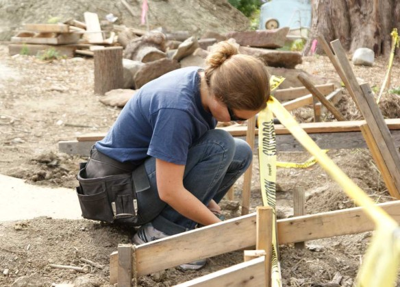 Hannah helped disassemble the batter boards and concrete forms. It was her first time wearing a tool belt.