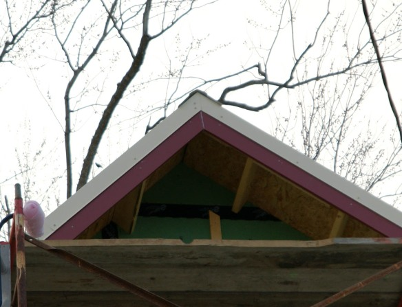 The gable peak has the metal roof wrap around the fascia boards.