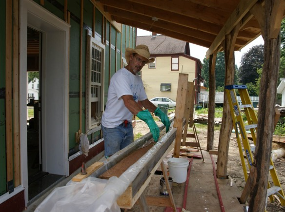 Andy dipping red cedar tongue and groove siding board in trough of Penofin stain