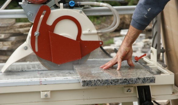 Using our wet cutting saw to cut granite counter top scrap